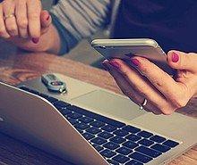 Frau sitzt am Laptop und schaut auf ihr Smartphone